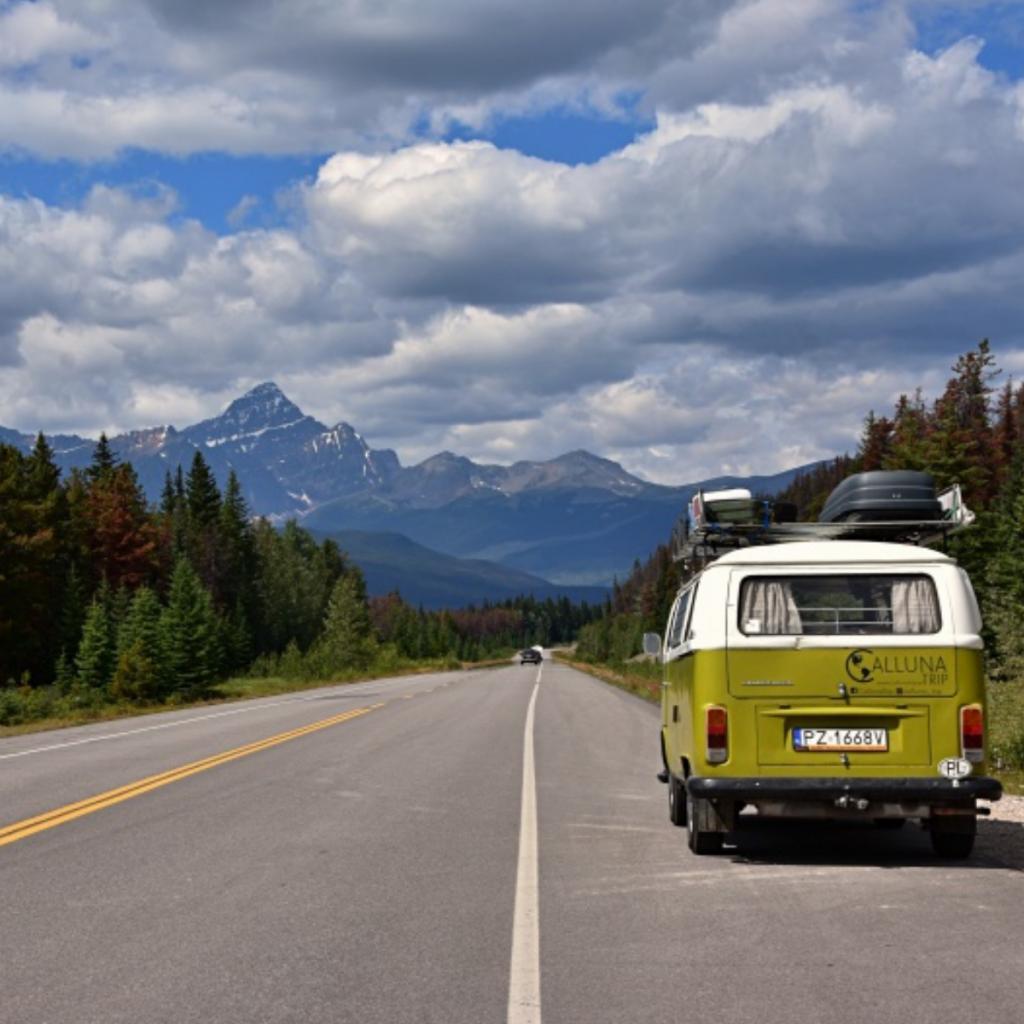 Kanada - Góry Skaliste. Zdjęcie przedstawia drogę Icefield Parkway. Na poboczu zaparkowany samochód marki VW Transporter Ogórek. Po bokach drogi lasy iglaste na horyzoncie góry.