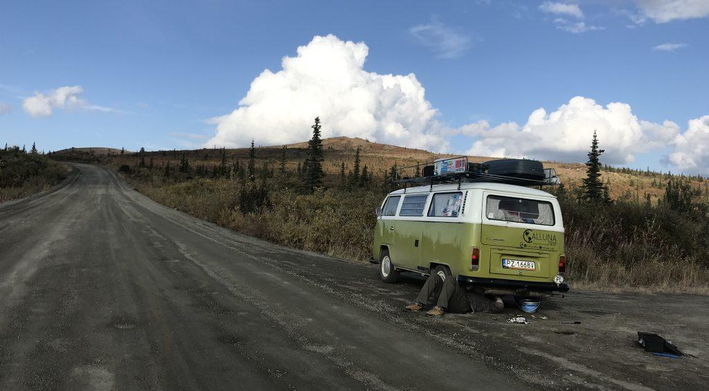 """Droga """"top of the world"""" na granicy Yukonu i Alaski. Zdjęcie przedtsawia mężczyznę naprawiąjącego samochód marki Volkswagen"""